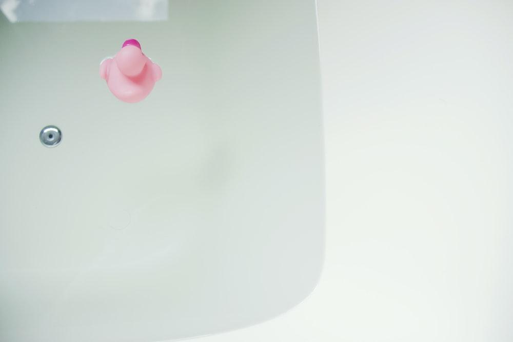 pink rubber duck on bathtub